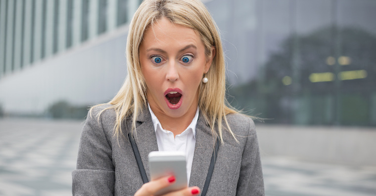 Surprised business woman looking at her smartphone