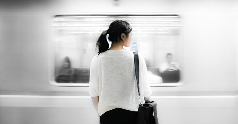 zena stoji a ceka vlak